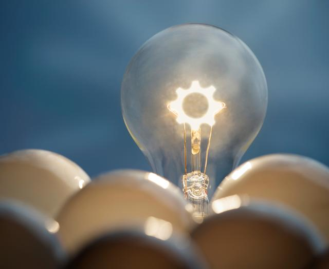 A light bulb that is on sits above a pile of light bulbs that are off