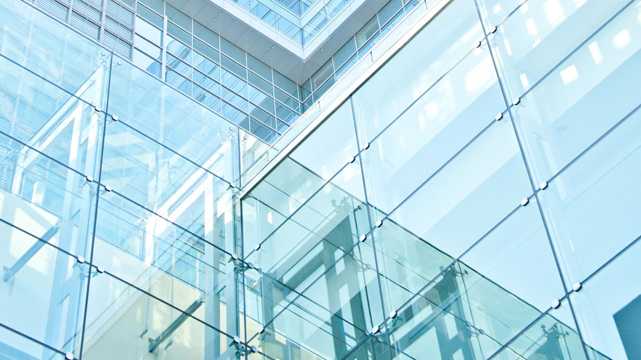 An upward view of the exterior of a glass paneled building