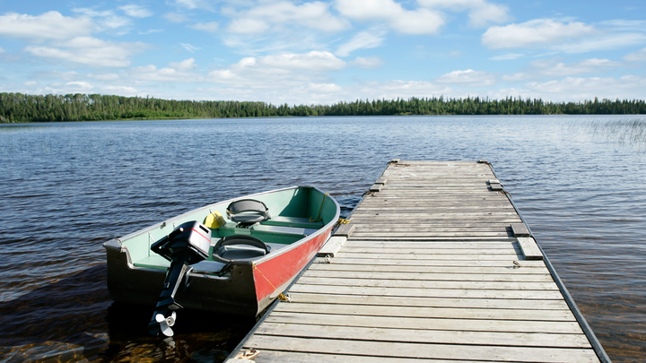 A boat and dock overlooking a lake with pine trees