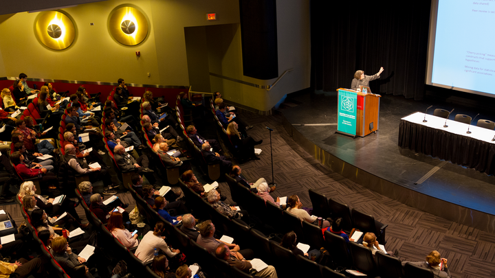 Research ethics conference attendees in the audience listen to plenary speaker on stage