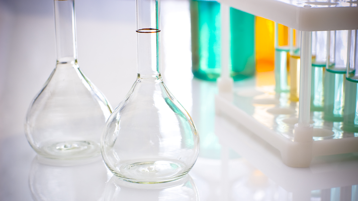 Test tubes with green liquid and empty flasks on a laboratory table