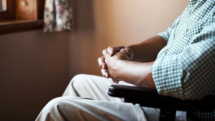 A man sits in a wheelchair facing a window